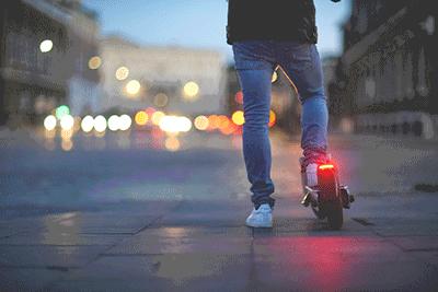 Ein Mann steht mit einem E-Scooter in der Dämmerung in der Stadt. Man sieht nur seine Beine und den E-Scooter von hinten.
