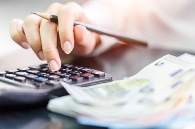Frauenhand mit Taschenrechner, Euro-Geldscheinen und Bleistift