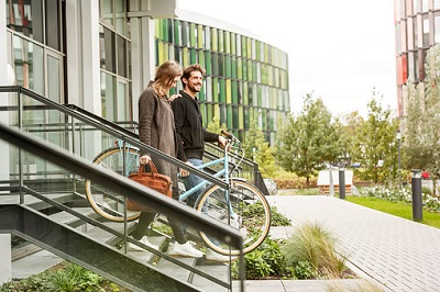 Junges Paar mit Fahrrad auf einer Treppe.