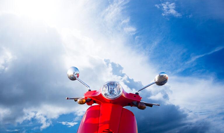 Ein rotes Moped steht vor blauem Himmel mit Wolken.