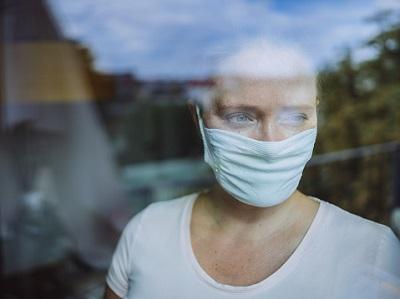 Frau schaut mit Maske während Corona-Pandemie aus dem Fenster.