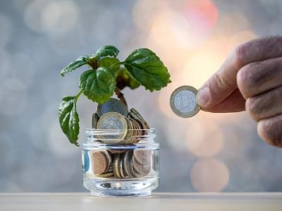 Hand legt Euro-Münze in Sparglas mit Pflanze.